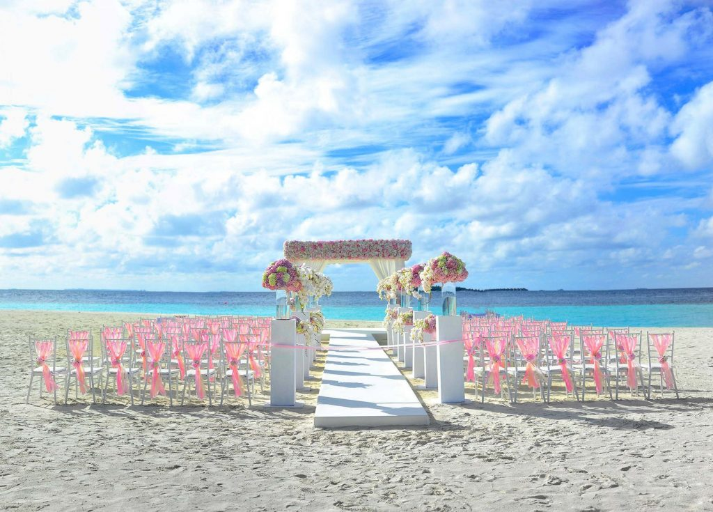outdoor wedding on the beach with floral aisle
